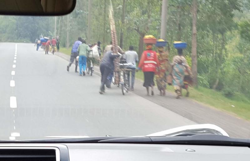 Gruppi di persone in cammino lungo la strada verso il mercato